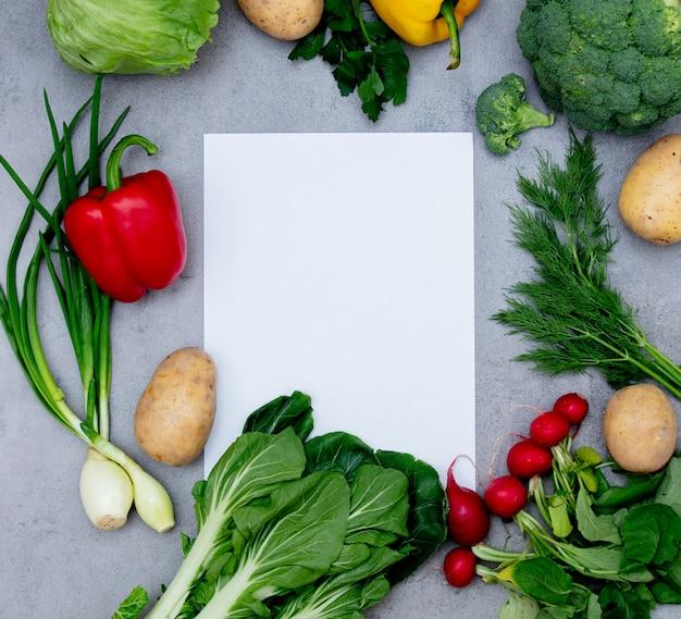 ホワイトペーパーとテーブルの上の野菜。