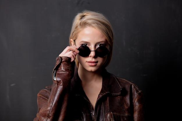 Красивая белокурая женщина в солнечных очках и куртке стиля