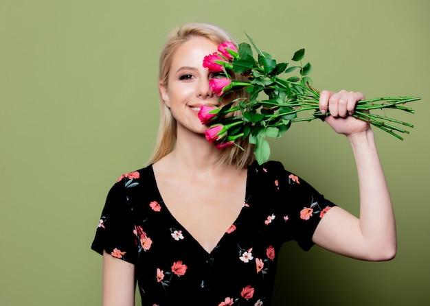 緑の壁にバラのドレスで美しい金髪の女性