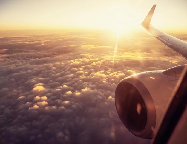 雲の上の日没時間で飛行機の翼に表示します。