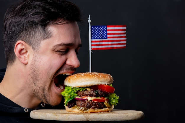 Парень ест классический американский бургер