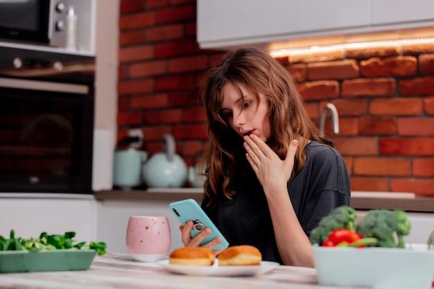 Грустная девушка использует телефон на кухне