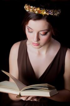 Молодая девушка брюнет с венком и книгой