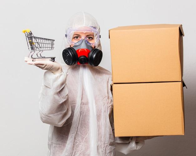 Почтальон в защитном костюме и очках с маской держит коробки для доставки и корзину