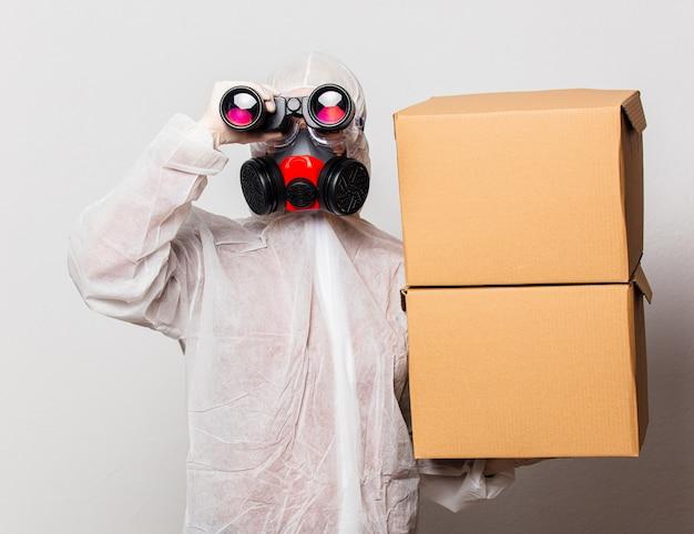 Женщина почтальон в защитном костюме и очках с маской держит коробки доставки и бинокль