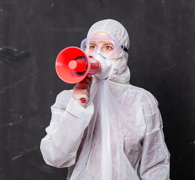 Женщина-врач в защитном костюме и очках с маской держит мегафон
