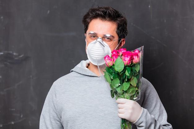 Влюбленный мужчина в маске держит букет роз