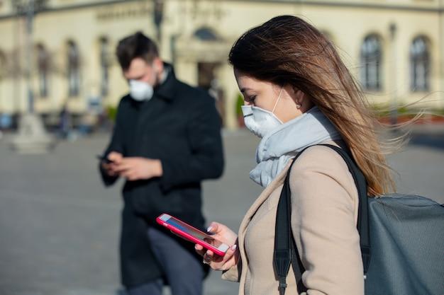 Женщина и парень в масках с помощью мобильного телефона