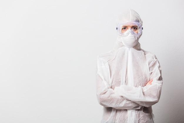 保護スーツと白い背景の上のマスクとメガネの若い医者