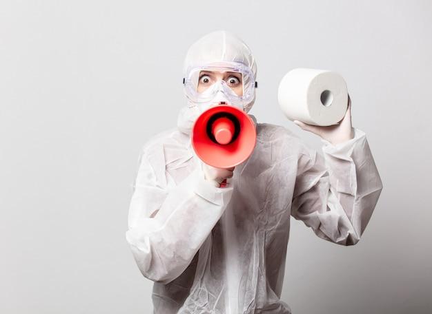 Доктор в защитном костюме и очках с маской держит мегафон и туалетную бумагу