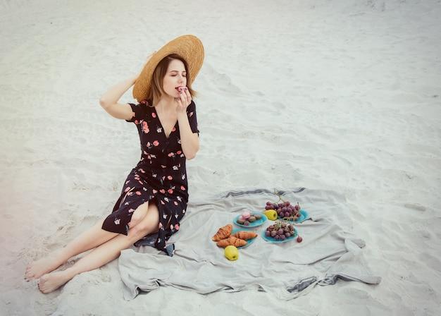 美しい女性は海の近くのビーチで一休みします。