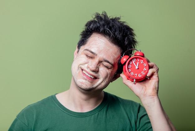 きれいなマスクと赤い目覚まし時計を持つ男