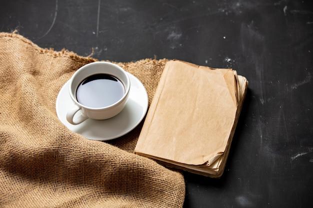 一杯のコーヒーとヴィンテージの本のテーブル