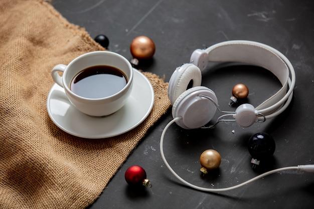 Чашка кофе и безделушки с наушниками