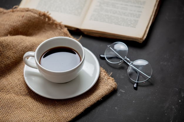 一杯のコーヒーとグラスが付いている本