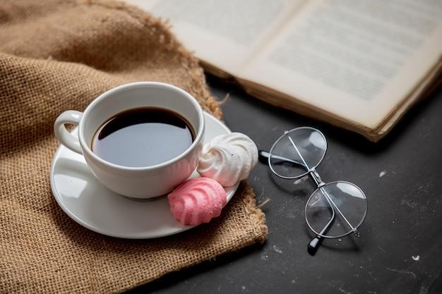 一杯のブラックコーヒーとグラスが付いている本