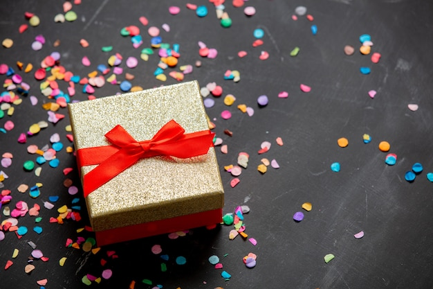 Золотая подарочная коробка с красной лентой и конфетти вокруг