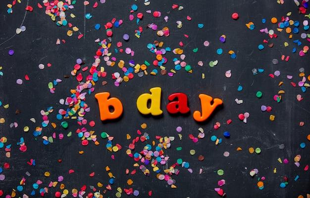 День рождения письма и конфетти вокруг на столе