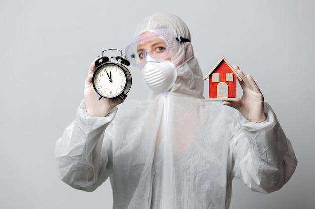 Медик в защитной одежде и будильнике просит вас остаться дома