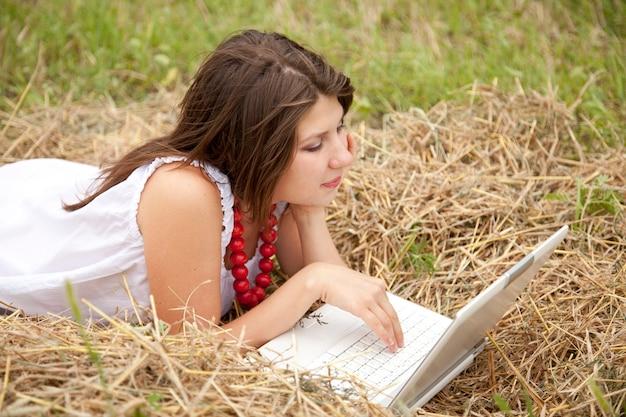 フィールドで横になっているノートブックと若者のファッションの女の子