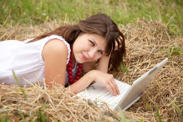 Молодая девушка моды с ноутбуком, лежа на поле