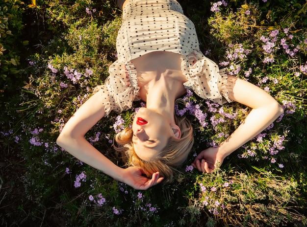 Белокурая девушка лежа на траве с цветками на сельской местности в заходе солнца