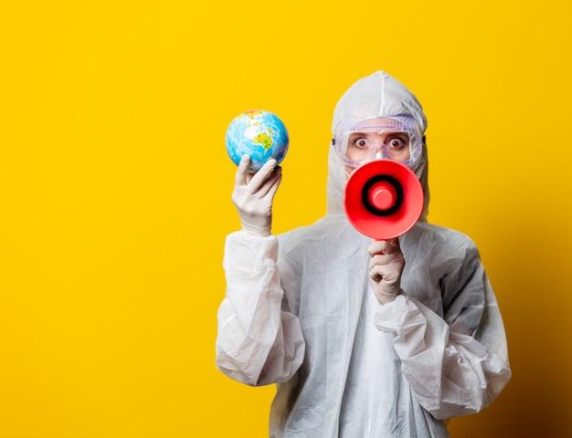 Медик в защитном костюме и маске держит земной шар и мегафон