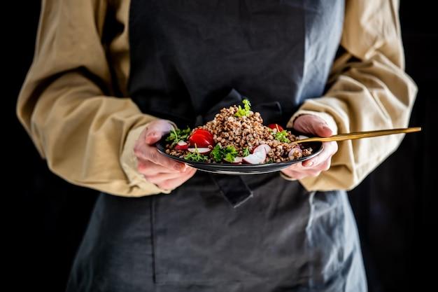 エプロンを着た女性が手にそばの皿を握る