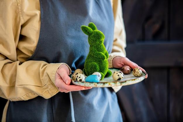 エプロンの女性は緑の装飾的なイースターのウサギと卵を保持しています。