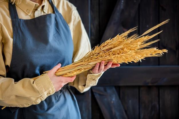 Самка в фартуке держит колоски пшеницы