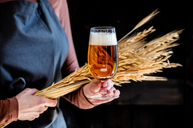 Пивовар в фартуке держит стакан пива и колоски пшеницы