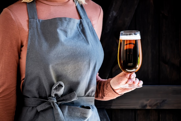 Пивовар в фартуке держит бокал пива