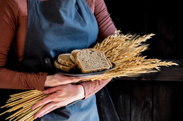 Женщина в фартуке держит колоски пшеницы и хлеб