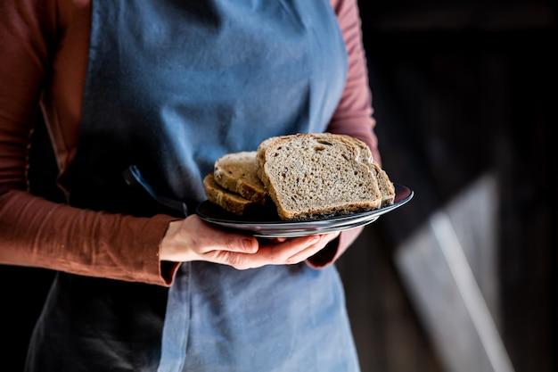 Женщина в фартуке держит тарелку с нарезанным хлебом