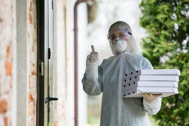 Доставщик в защитном костюме с пиццей возле двери