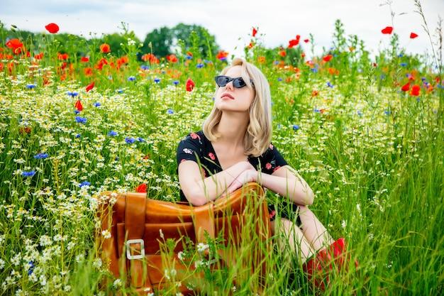 夏にはポピーフィールドでスーツケースを美しいドレスでブロンドの女の子
