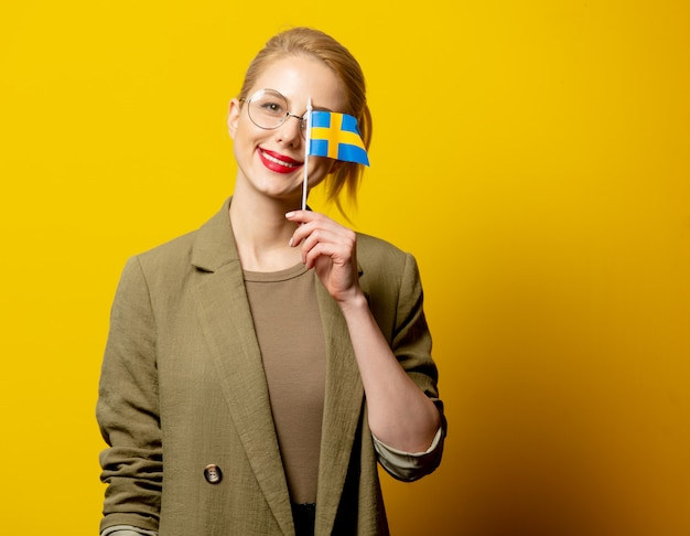 Стильная блондинка в куртке со шведским флагом на желтом