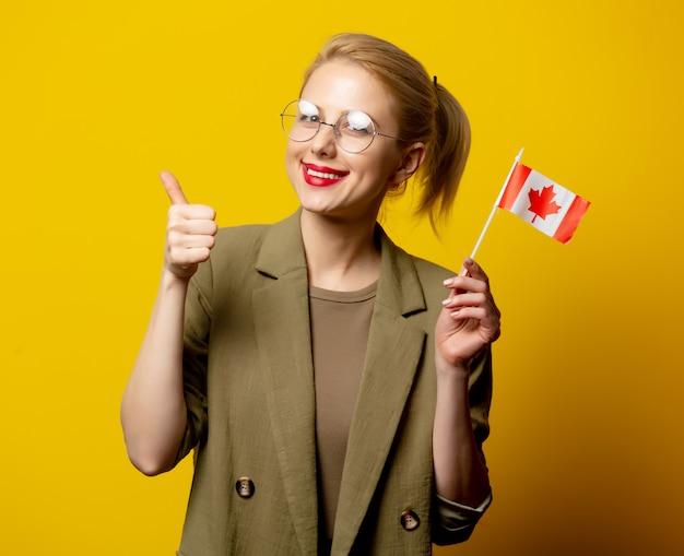 Стиль блондинка в куртке с канадским флагом на желтом