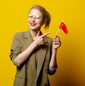 黄色の中国の旗のジャケットのスタイルのブロンドの女性