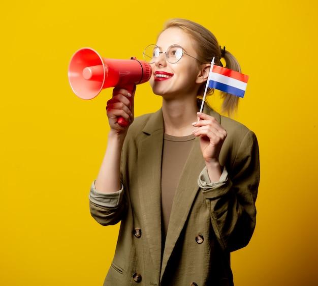 オランダの旗と黄色のメガホンのジャケットのスタイルのブロンドの女性