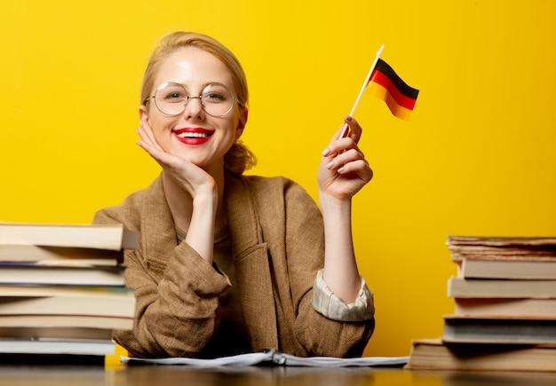 Стиль блондинке, сидя за столом с книгами и флагом германии на желтом