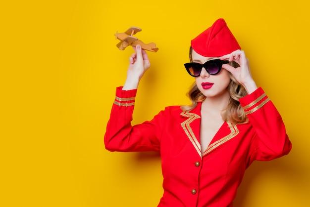 飛行機で赤い制服を着て魅力的なビンテージスチュワーデス