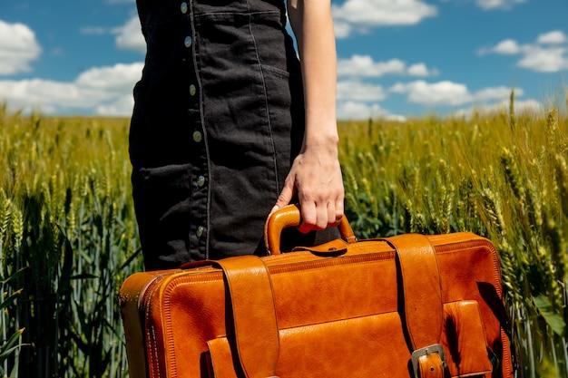 手でクローズアップビューは麦畑の近くの田舎道でスーツケースを保持します。