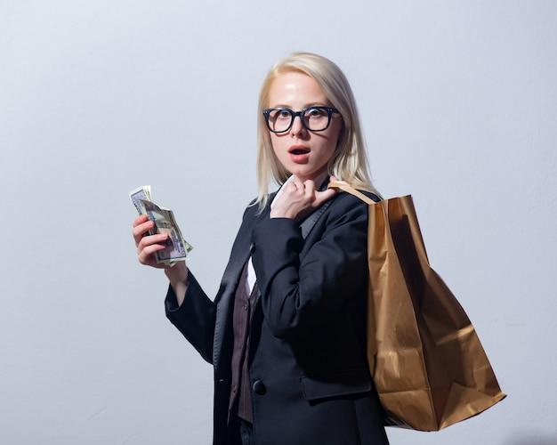 Красивая белокурая коммерсантка в костюме с хозяйственной сумкой и деньгами