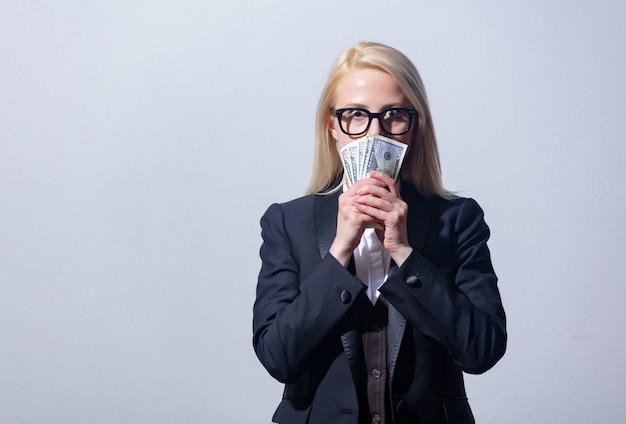 Красивая блондинка предприниматель в костюме с деньгами на сером фоне