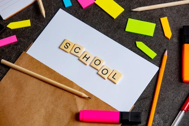 Школьные буквы на листе бумаги и заметки вокруг на столе
