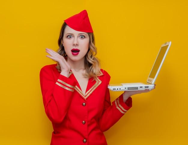ラップトップコンピューターと赤い制服を着てスチュワーデス