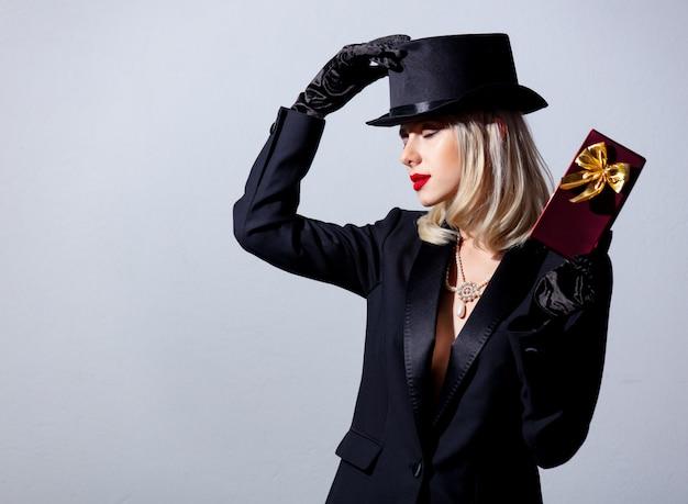 黒いジャケットと白い壁のギフトボックスとシルクハットのブロンドの女性
