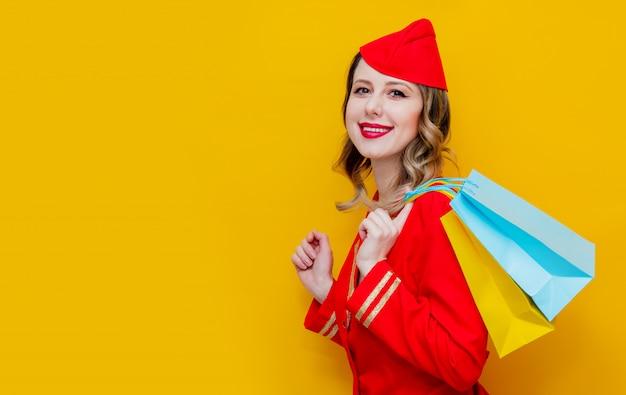 Стюардесса в красной форме с сумками.
