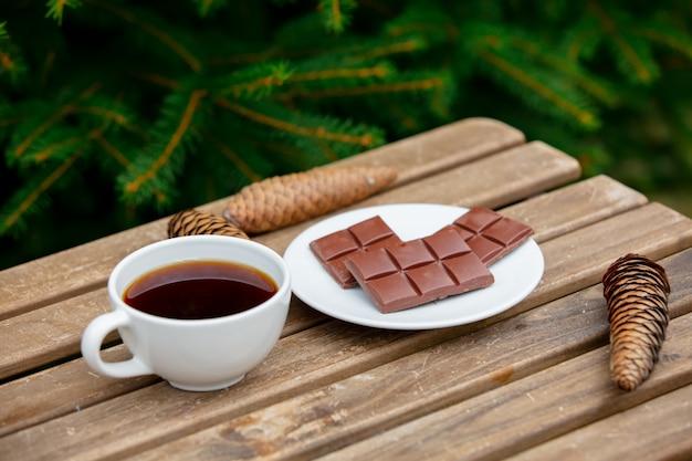 背景にトウヒの枝と木製のテーブルの上のコーヒーとチョコレートのバーのカップ